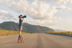 A young boy dressed in paper boy hat and retro attire stands on a stool calling out his message through a megaphone. He is on a rural road in the mountains of Utah County, Utah, USA.