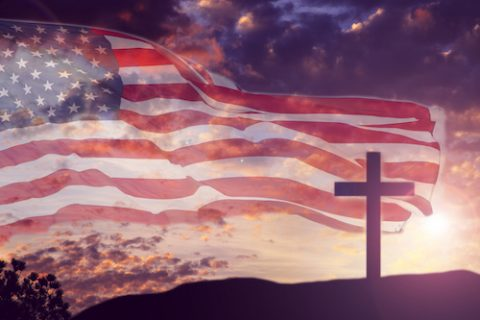 USA flag overlay on dramatic purple sunset sky with one Christianity cross standing on a hill for Good Friday, Easter holidays.